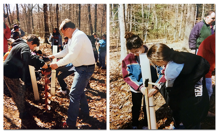 Two photographs showing students planting tree saplings in the historic tree grove at Armstrong Elementary. In the photograph on the left, a boy and a man work an awl into the ground as a group of students stand in the background. In the photograph on the right, two girls have placed a protective sleeve around a sapling and are hammering a wooden support stake into the ground next to the tree. The planting was done during the autumn as the leaves have fallen off of the trees and the ground is covered with dry brown leaves.